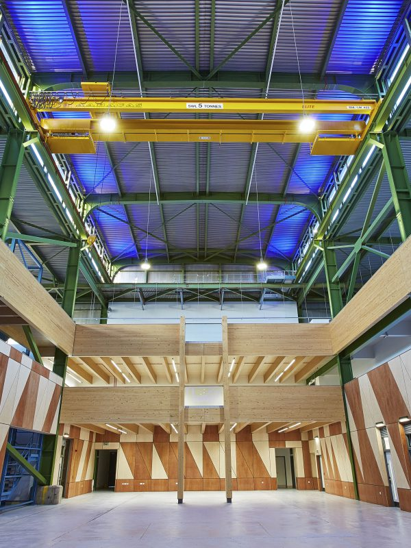 Prefab Offsite Industrial Conversion - yellow crane, blue lights, steel frame, laminated timber structure and plywood cladding.